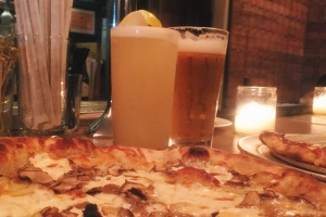 Drinks rising from a landscape of pizza